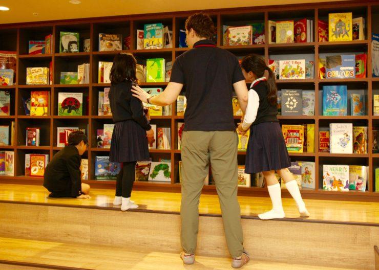 ネストンキッズアフタースクールの書棚の前で本を選ぶ子供たち